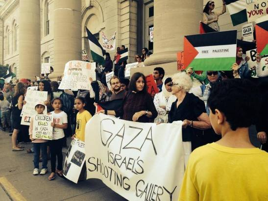 The image is of a protest held in Kingston to show solidarity with Gaza. Description of image below.