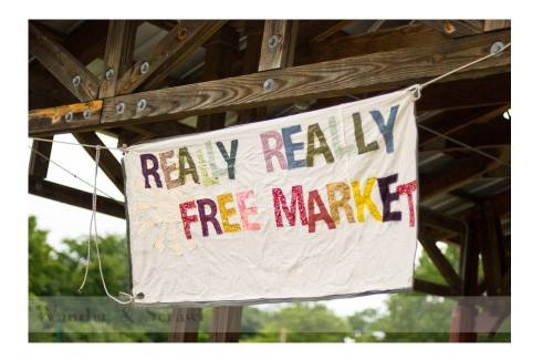 Image is a photograph of a canvas sign that reads 'Really Really Free Market']